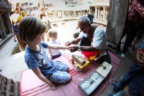 monk putting on bracelet, faces of angkor wat, faces of cambodia, cambodian kids